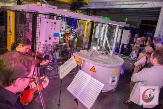 Chris Huber (vo. li.) und Barbara Buntrock (dahinter) musizierten in den illuminierten Berger-Betriebshallen mit einemRoboter. | Foto: Marcus Müller
