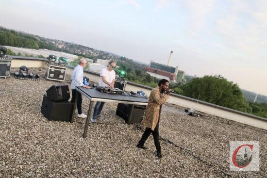 Einheizen im Schatten des Müllheizkraftwerkes: Sänger Tony T mit den DJs Kribz und Chris Zilles (v.r.n.l.) bei ihrem Streaming-Gig für die guten Zwecke auf dem Dach des Schulzentrums Süd.   Foto: Meinhard Koke